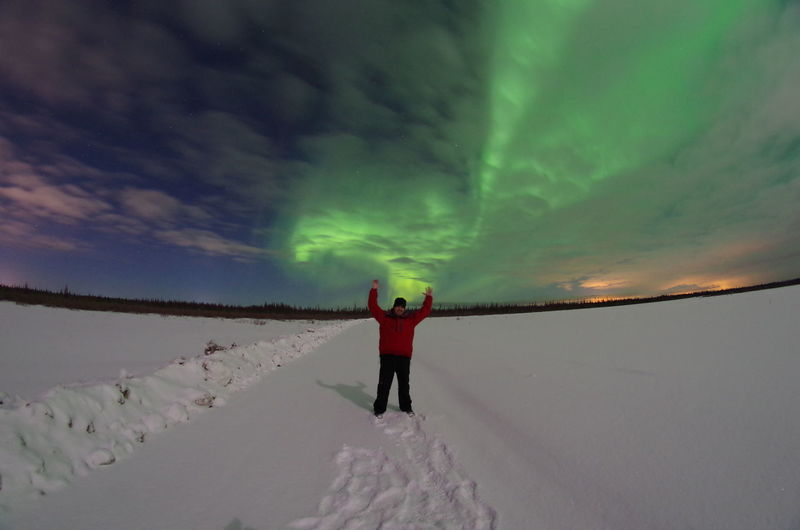 Portrait Of Man With Arms Raised, Aurora Borealis In Sky