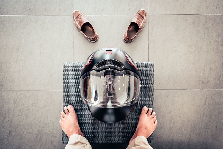 Low Section Of Man Standing By Helmet On Mat