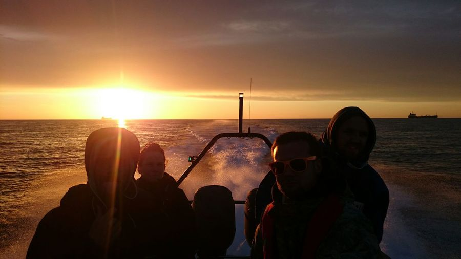 Friends Enjoying In Boat On Sea Against Cloudy Sky During Sunset