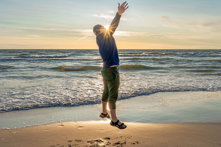 Full length of man jumping with arms raised at beach during sunset