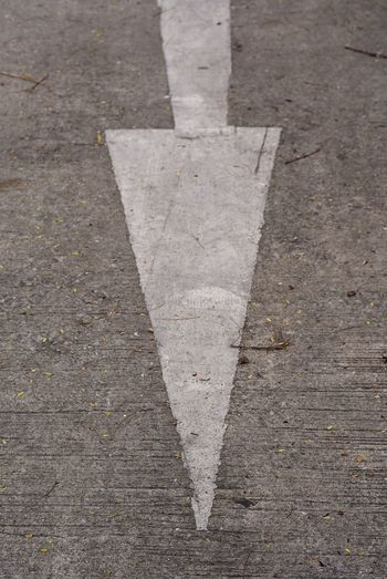 Directly above shot of arrow symbol on road