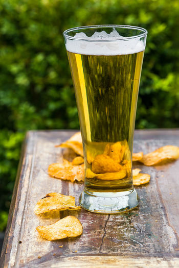 Beer and crisps on the table in the garden Beer Beer - Alcohol Beer Glass Close-up Day Drink Drinking Glass Food And Drink Freshness Frothy Drink Frothy Drink Latte Garden Gold Colored Nature No People No People, Outddoor Outdoors Sweet Food Table Visual Feast