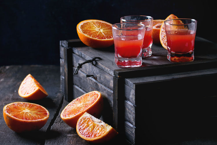 Shorts of alcohol cocktail with Sliced Sicilian Blood oranges and fresh red orange juice, served on black wooden chest over old wooden table. Dark rustic style. Black Background Juice Sicilian Orange Alcoholic Drink Bloody Orange Citrus Fruit Cocktail Cocktails Dark Photography Drink Drinking Glass Food Food And Drink Freshness Fruit Fruit Juice Glass Healthy Eating Orange Orange - Fruit Orange Color Refreshment Ripe Shorts SLICE
