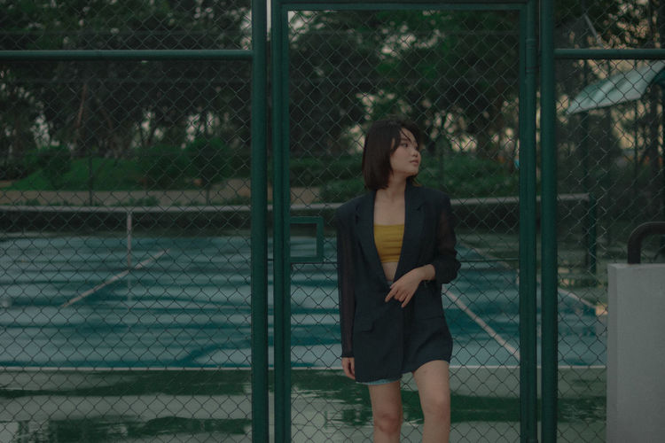 Full length of woman standing by chainlink fence