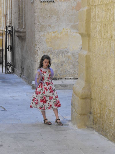 A girl in an old town Full Length One Person Architecture Looking At Camera Females Women Portrait Childhood Child Day Standing Built Structure Girls Front View Emotion Building Building Exterior Happiness Fashion Outdoors Architectural Column Innocence Hairstyle Old Town Malta