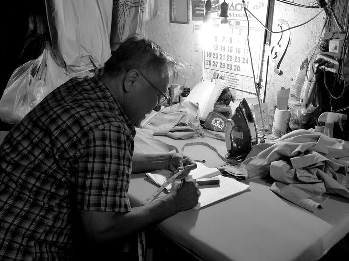 Tailor with tape measure writing in book
