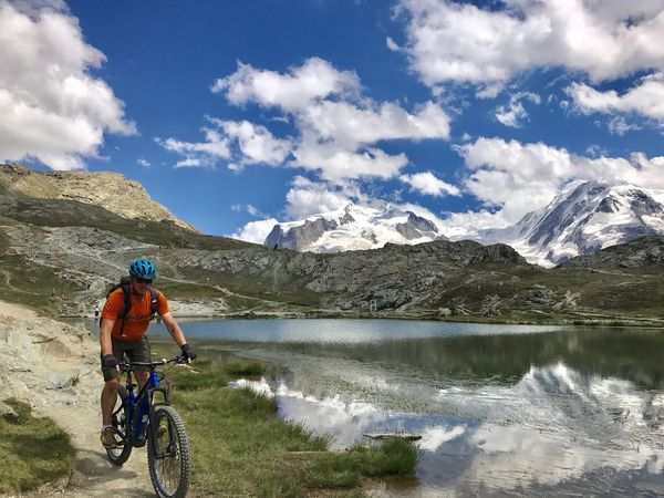 Adventure Beauty In Nature Bicycle Cloud - Sky Cycling Cycling Helmet Day Full Length Lake Landscape Leisure Activity Lifestyles Men Mountain Mountain Bike Mountain Range Nature One Person Outdoors Real People Rocky Mountains Scenics Sky Water Waterfront