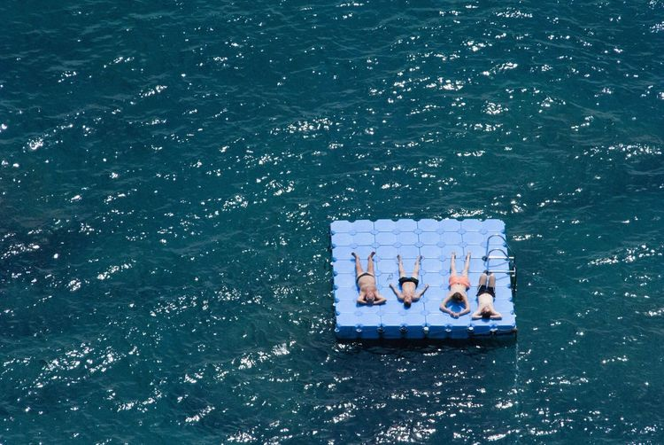 High angle view of shirtless friends relaxing on diving platform in sea