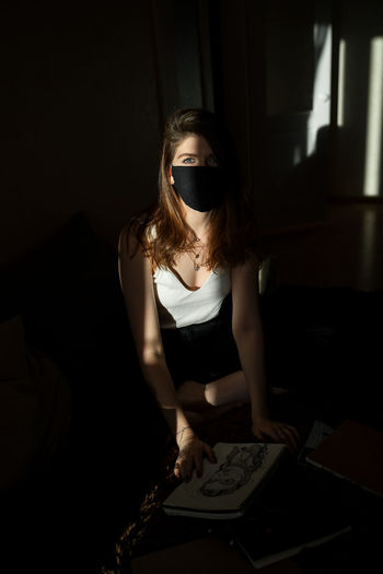 Portrait of woman wearing mask in darkroom