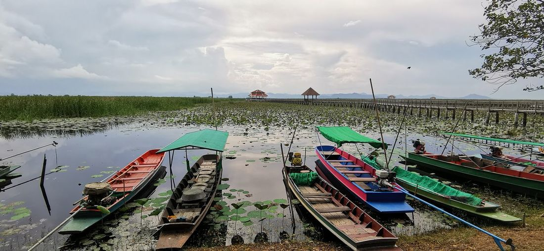 Panoramic view of boats moored in lake against sky