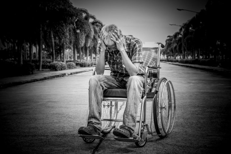 Depressed man with head in hands sitting on wheelchair