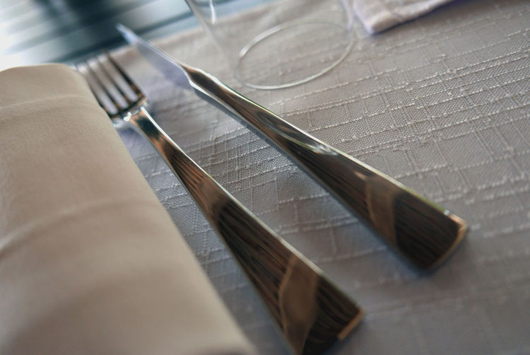 Close-Up Of Fork And Table Knife By Napkin On Table