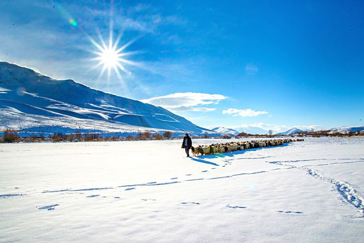 Woman walking on snow covered land against sky