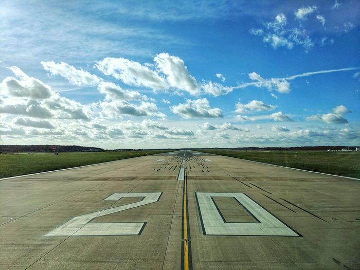 Numbers on airport runway against sky