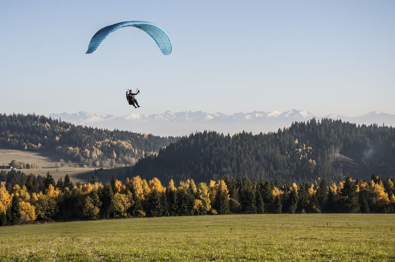 Low Angle View Of Mid Adult Man Paragliding Over Landscape Against Clear Sky