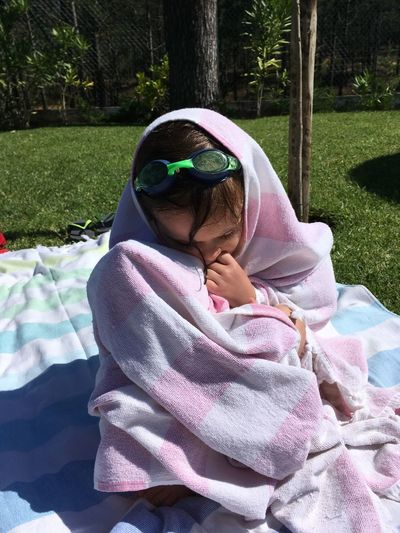 Girl Wrapped In Towel Sitting On Blanket During Sunny Day