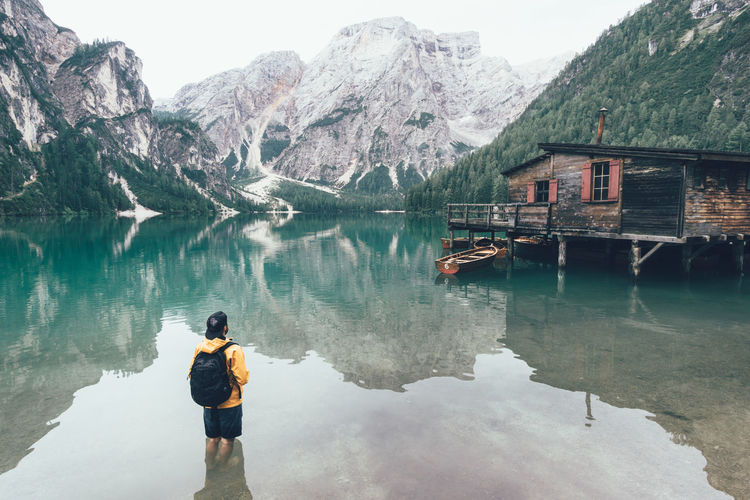Man in yellow jacket standing in the cold and crystal clear water of Lago di Braies mountain lake Adventure Travel Alps Alto Adige Dolomites Dolomiti Hike Hiking Italy Lago Di Braies Lake Man In Lake Mountain Lake Mountain Range Mountains Outdoor Lifestyle Pragserwildsee South Tyrol Standing Standing In Lake Standing In Water Stn Südtirol My Year My View Tranquility My Favorite Place
