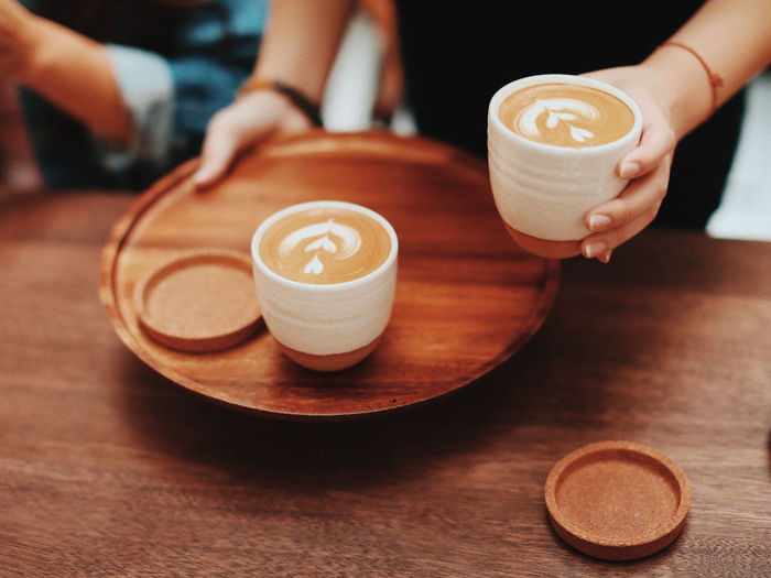 Cropped image of coffee cup with cappuccino served on table