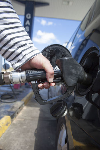 Close-Up Of Man Refueling Car At Petrol Pump