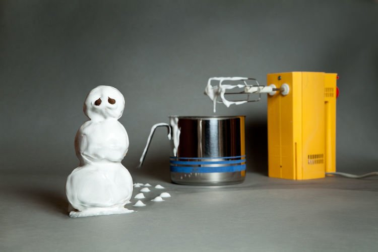 Snowman made with cream by grinder and container against gray background