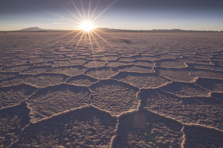 Scenic view of desert against sky at sunset