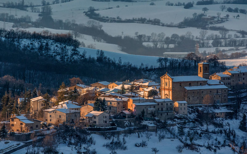 Aerial view of snow covered houses at sunset