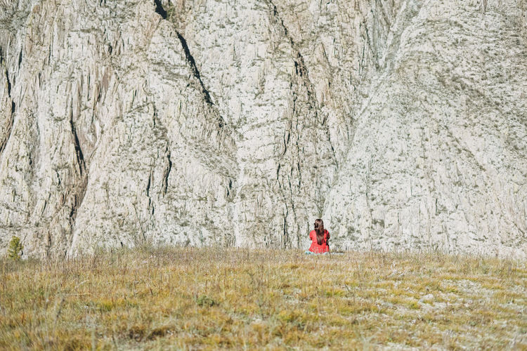 Small figure of young woman in red traveler back on mountais rock background