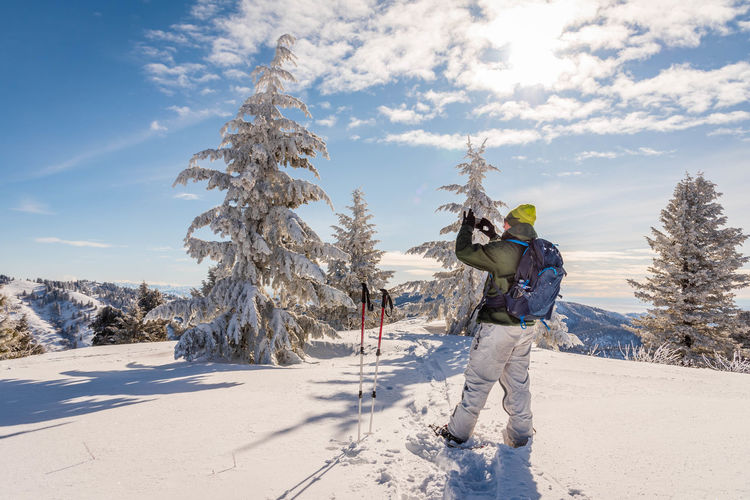 Rear view of man on snow covered mountain against sky