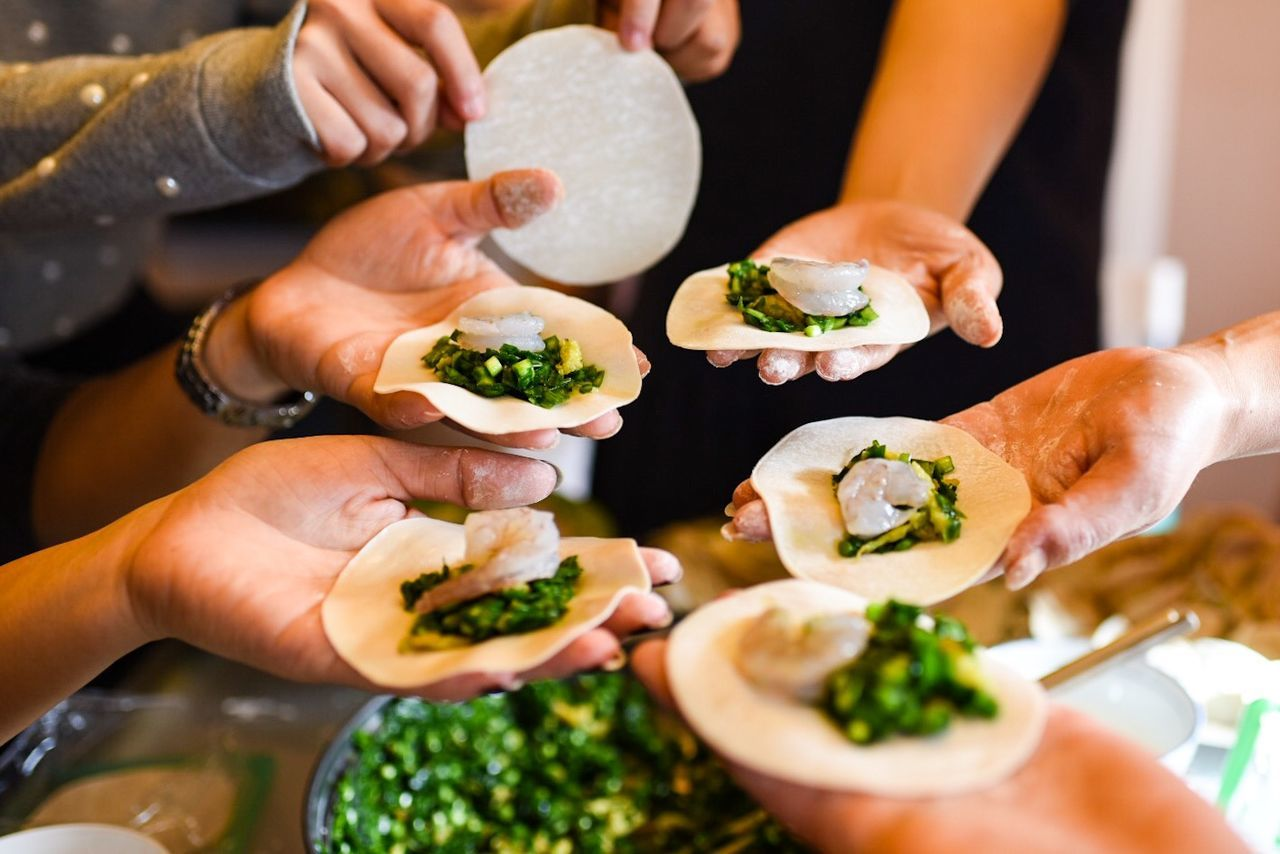Cropped image of hands holding dumplings