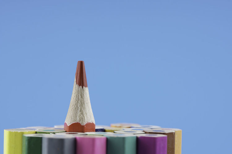 Close-up of colored pencils against blue sky