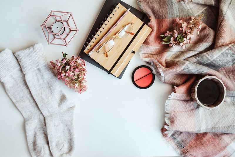 feminine winter table, woman fashion clothes and make up, sketch book and coffee. Seasonal set on white background. Indoors  Table Feminine  Style Style And Fashion Winter Wintertime Makeup Notes Morning Cozy At Home Cozy Cold Days Sweater Candle Autumn Pink Color Blanket