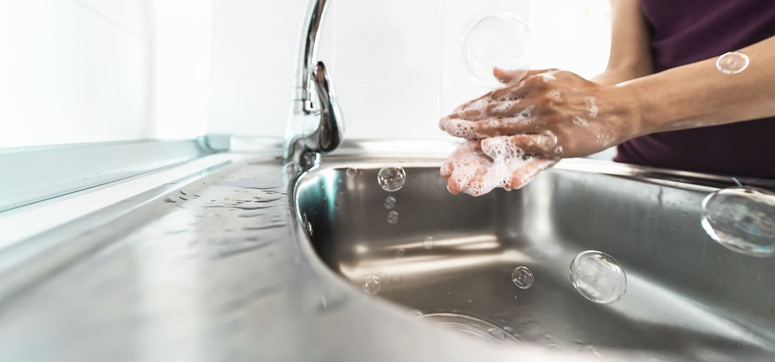 Midsection of person with reflection in water at home