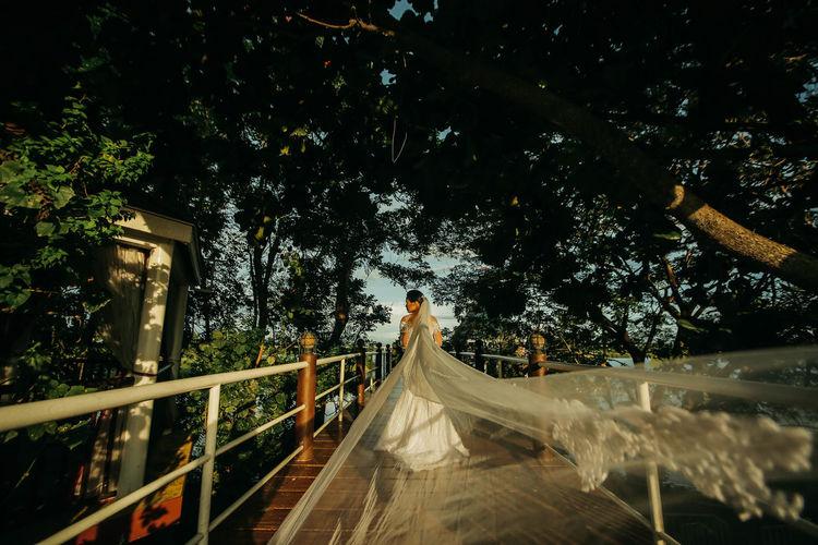 Bride standing by railing on bridge against sky