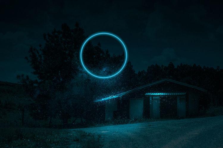View of illuminated circle against trees at night