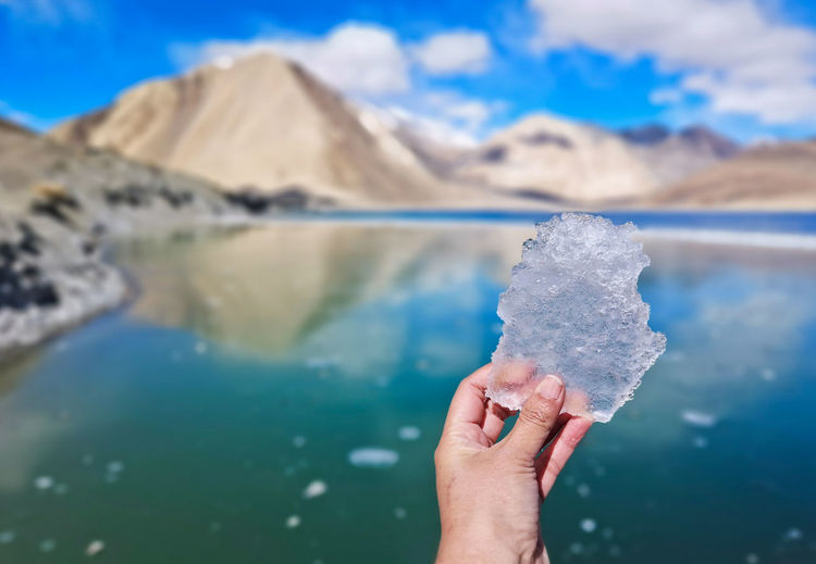 Close-up of person holding ice against lake