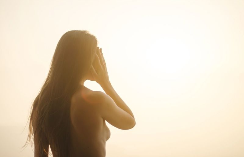 Rear view of woman standing against sky during sunset
