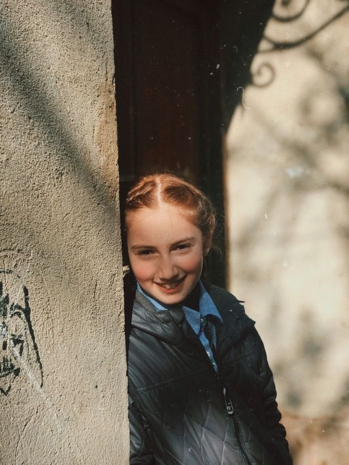 Portrait of smiling girl standing by wall