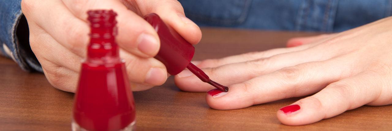 Midsection Of Woman Applying Red Nail Polish At Table