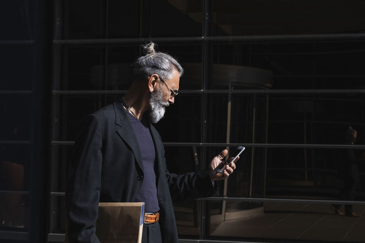 Man holding mobile phone while standing at home