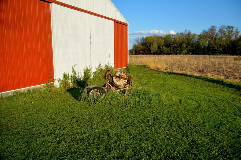 Old rusty cement mixer on grassy field by barn against sky