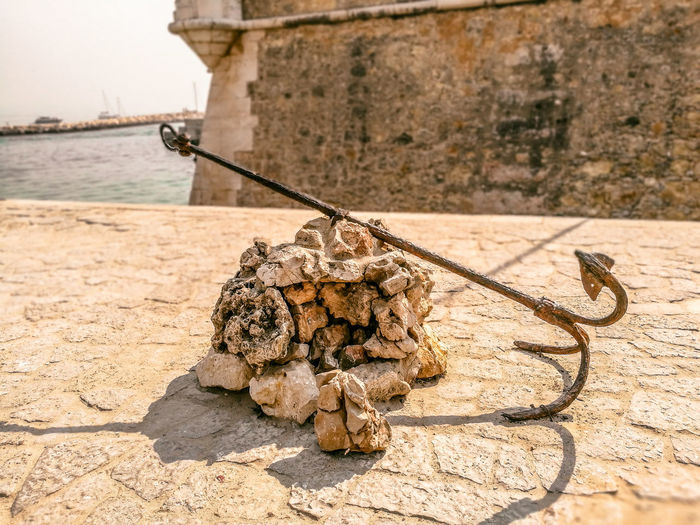 Close-up of anchor on stones at harbor