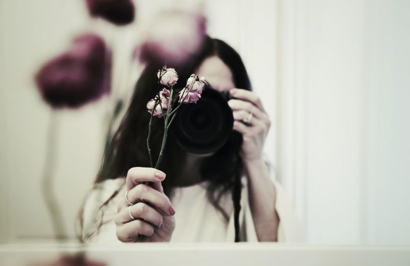 Woman photographing dry flowers while reflecting in mirror