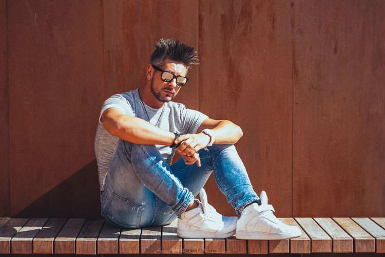 Casual Clothing One Person Sitting Glasses Young Men Full Length Eyeglasses  Lifestyles Real People Young Adult Wood - Material Leisure Activity Wall - Building Feature Front View Looking Portrait Men Holding Indoors  Flooring