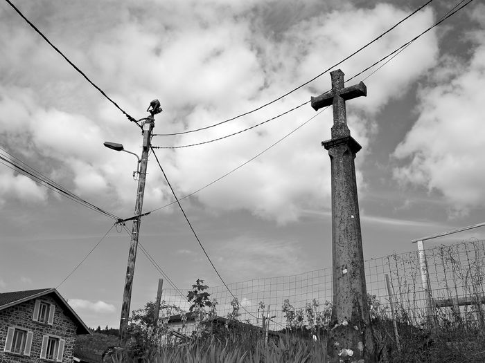 Low angle view of cross sculpture against cloudy sky at villefranche-sur-saone