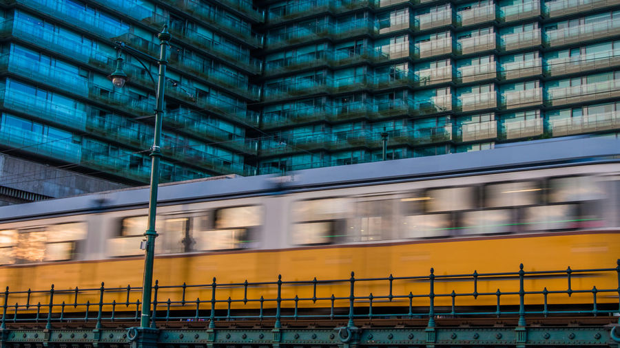 Blurred motion of train against building in city