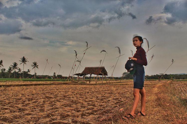 Full length portrait of boy standing on field against sky