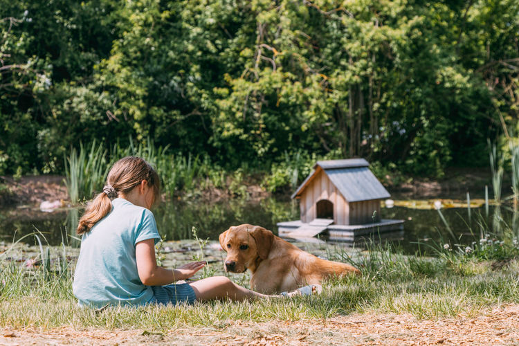 Friendship of animals and children. caucasian girl sits on of a pond and plays with  puppy, labrador