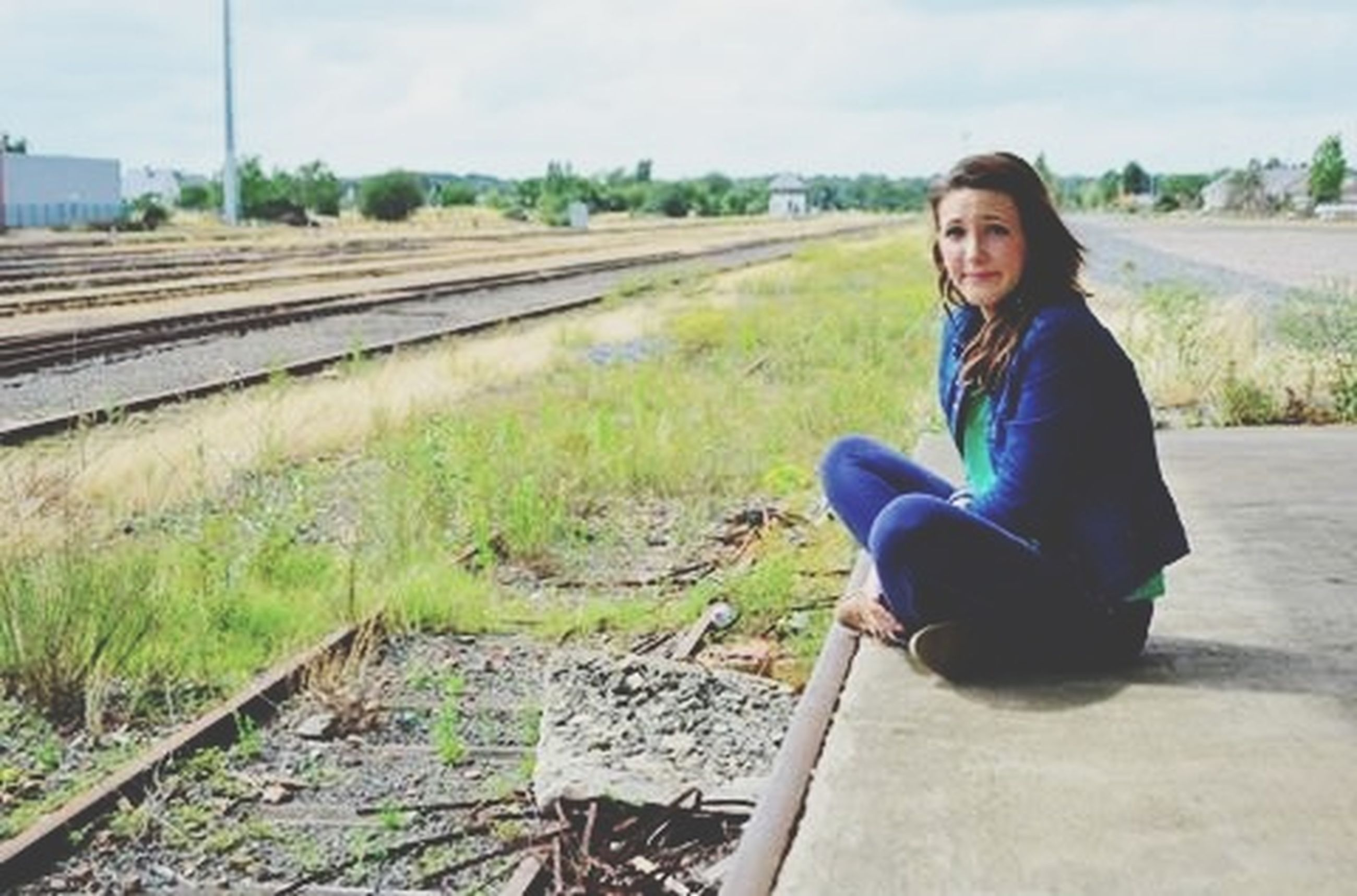 casual clothing, person, lifestyles, young adult, leisure activity, field, portrait, looking at camera, standing, grass, smiling, full length, railroad track, young women, sitting, front view, three quarter length