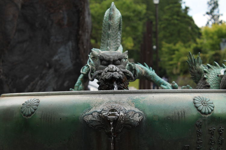 Close-Up Of Statue Fountain Against Trees In Garden