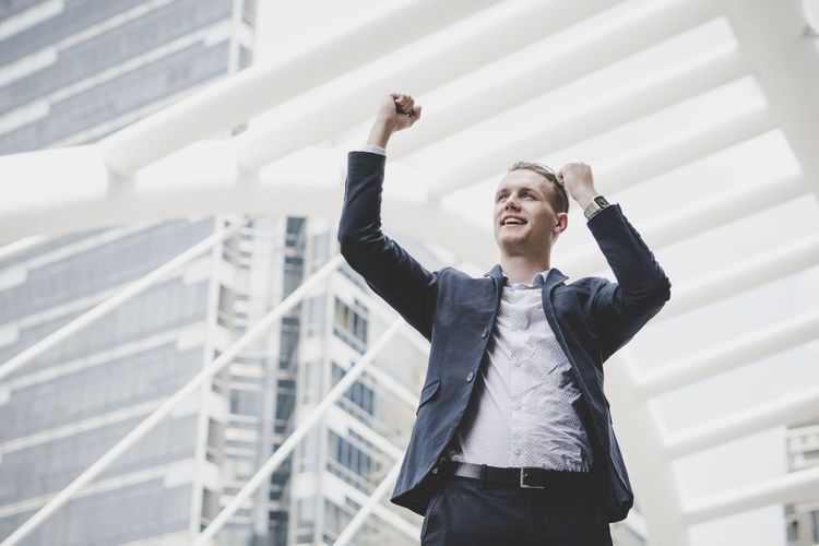 Businessman Standing With Clenched Fist Against Metallic Structure